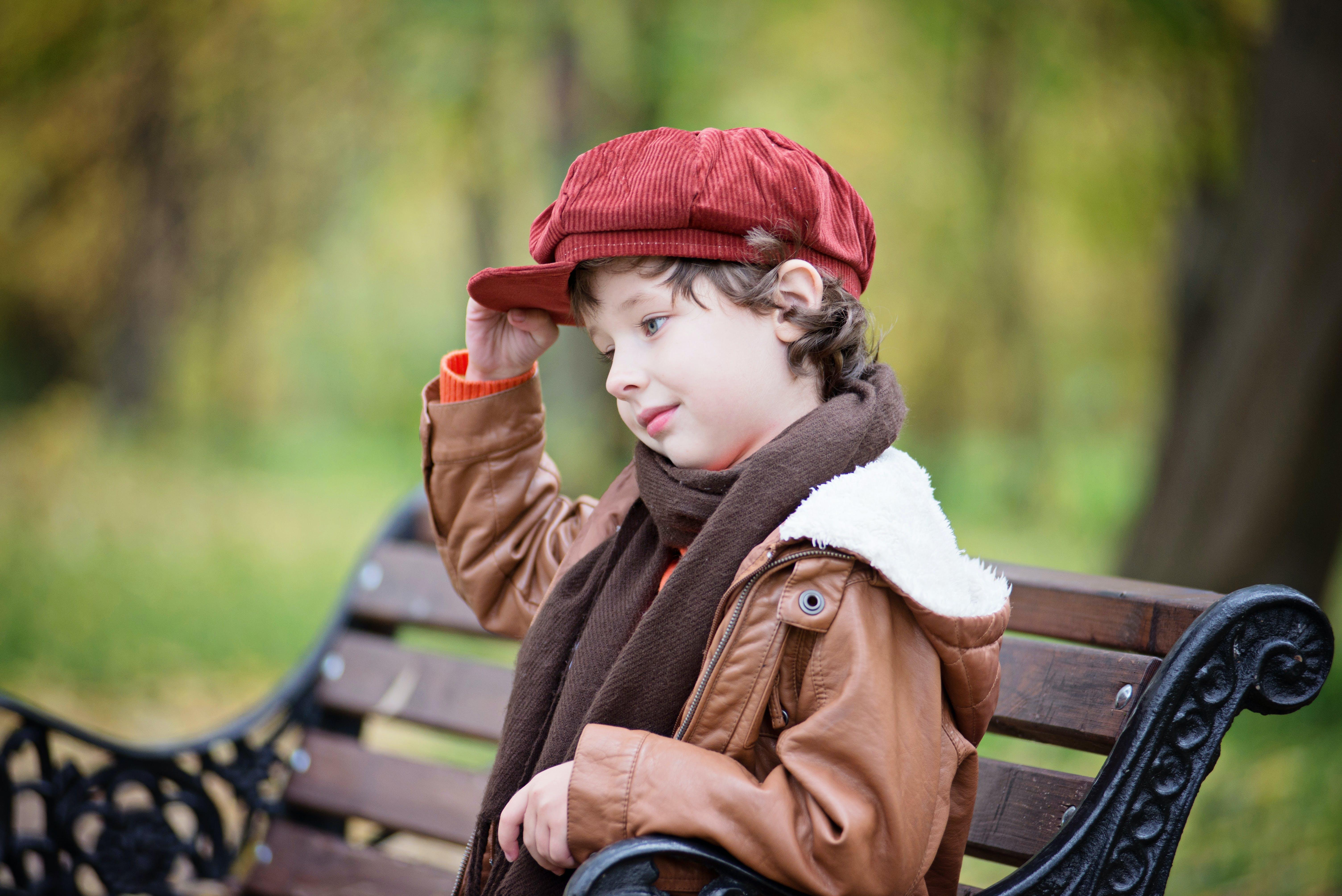 Boy Wearing Red Beret Cap While Sitting on Bench