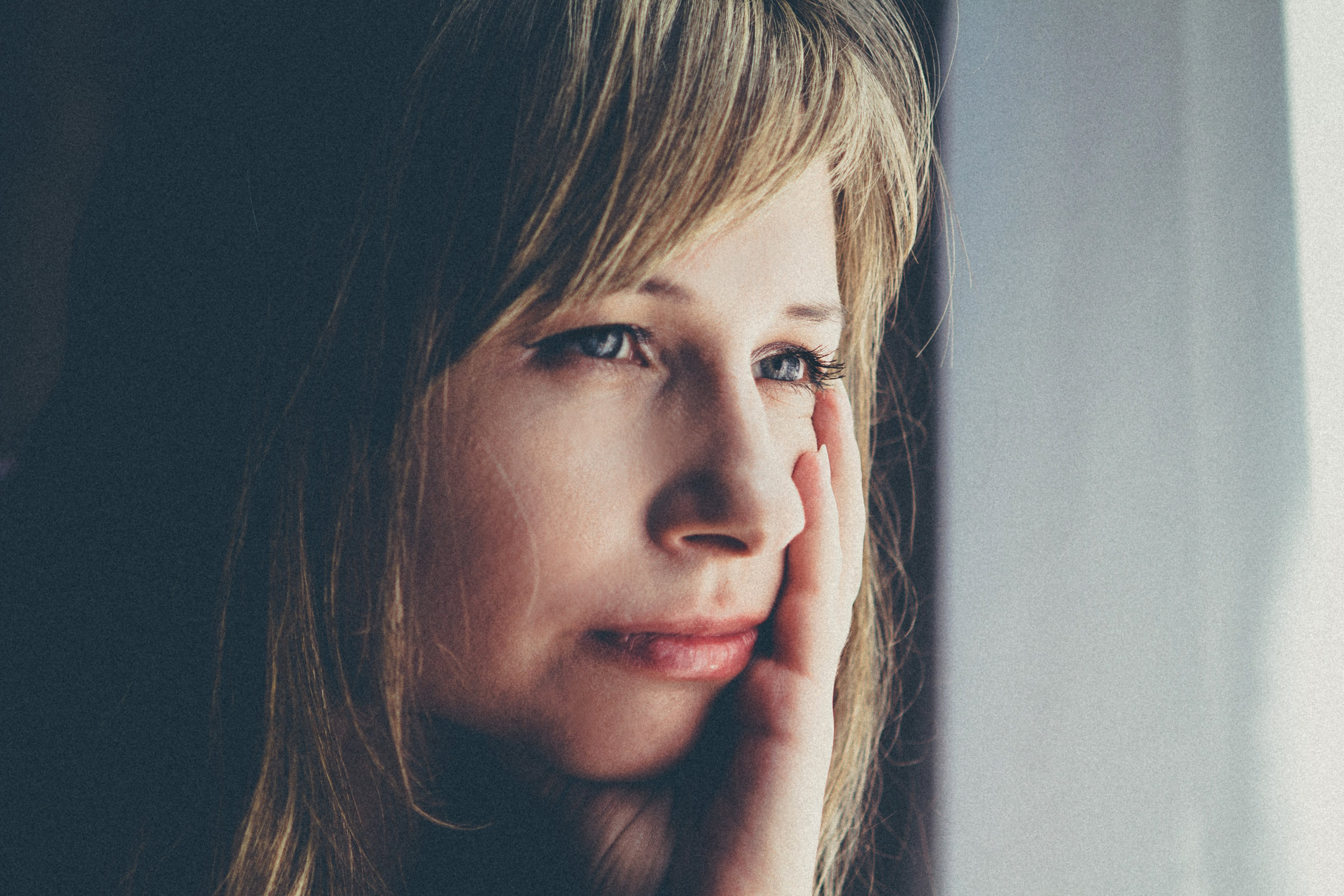 Shallow Focus Photography Of Woman Touching Her Left Cheek