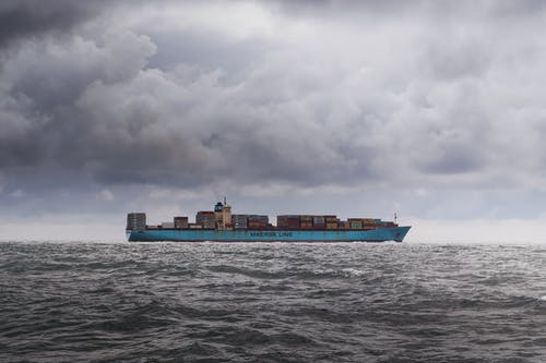 Blue Cargo Ship on Sea Under White Clouds