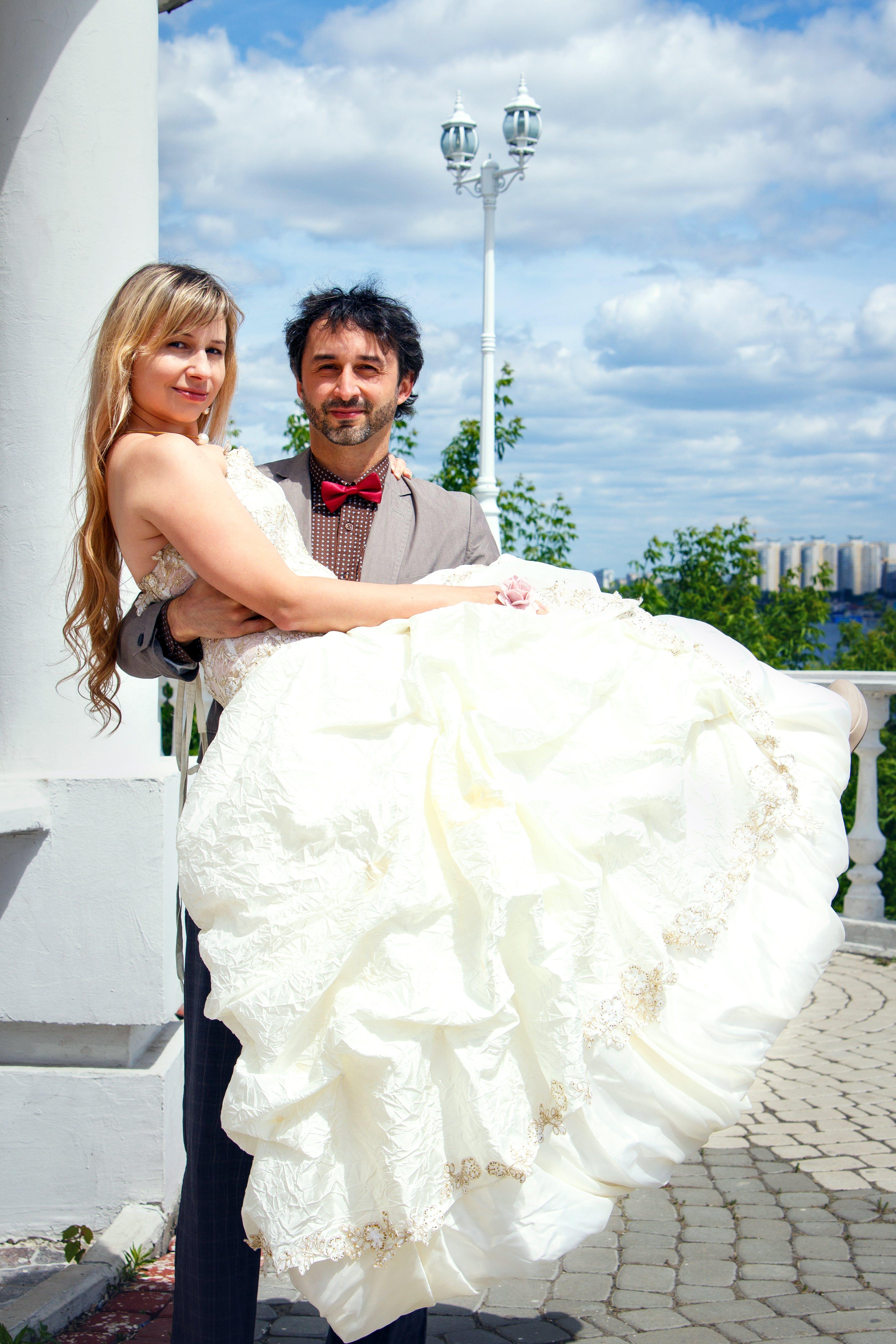 Man Carrying Woman in White Wedding Dress