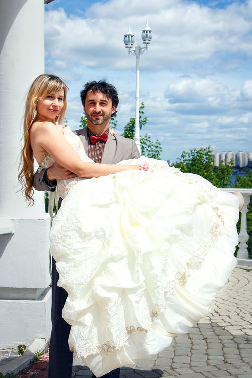 Man Carrying Woman in White Wedding Dress