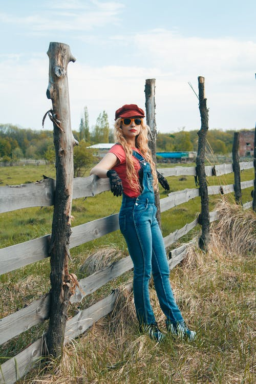 Woman Wearing Red Station Cap Beside Wooden Fence