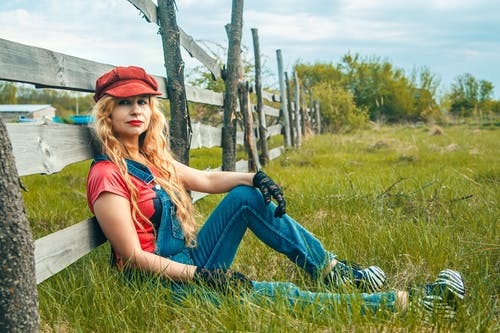 Woman Leaning on Wooden Fence Outdoors