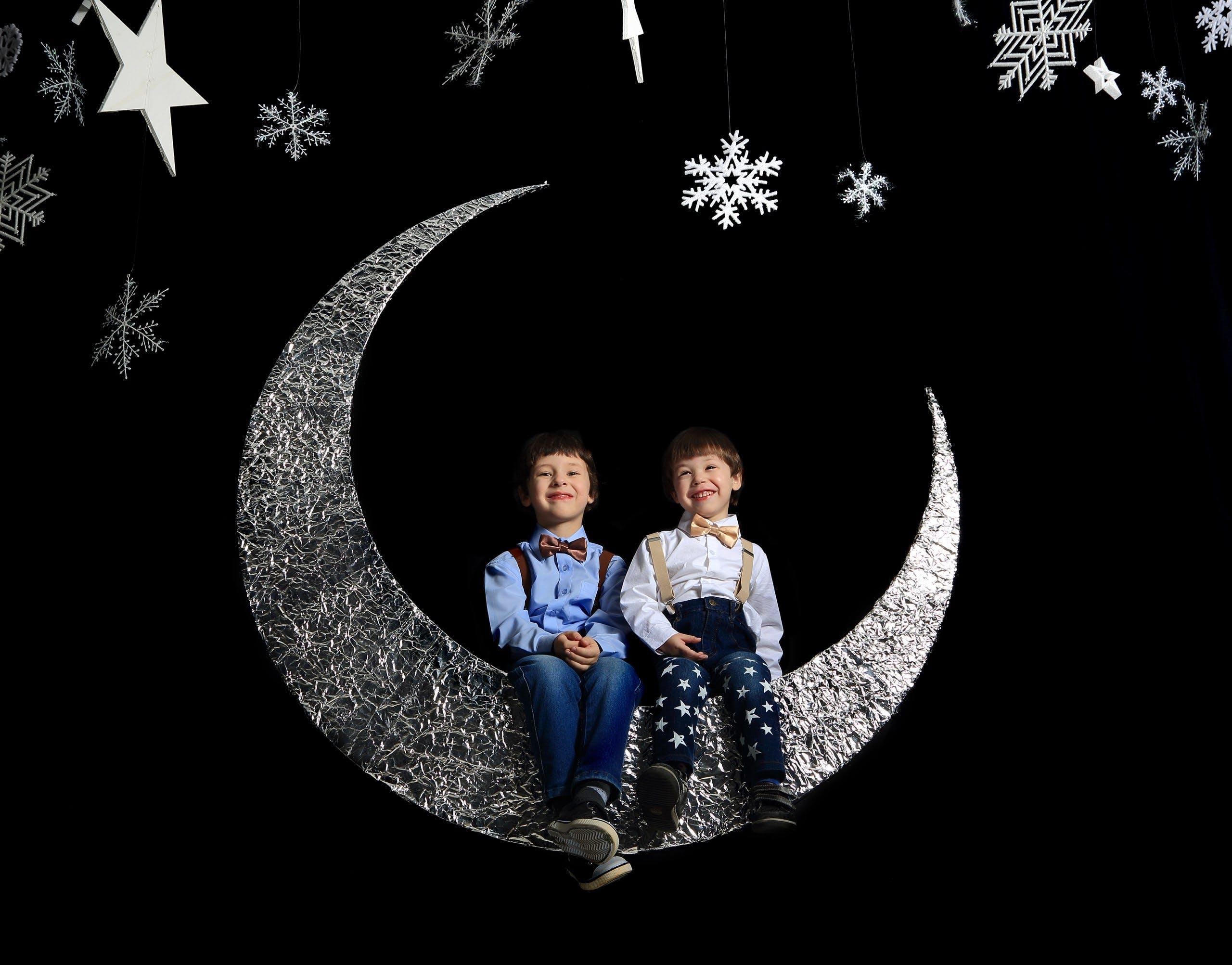 Jumeaux assis sur un croissant de lune | Photo : Pexels