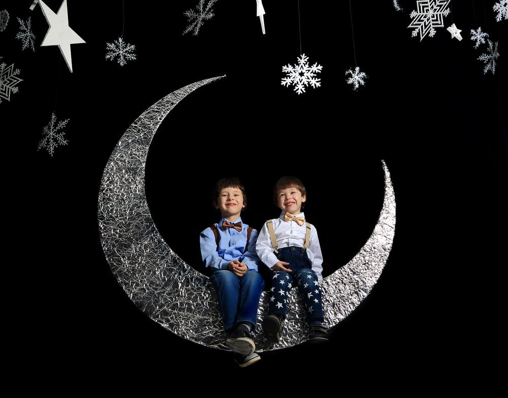 Twins sitting on crescent moon | Photo: Pexels