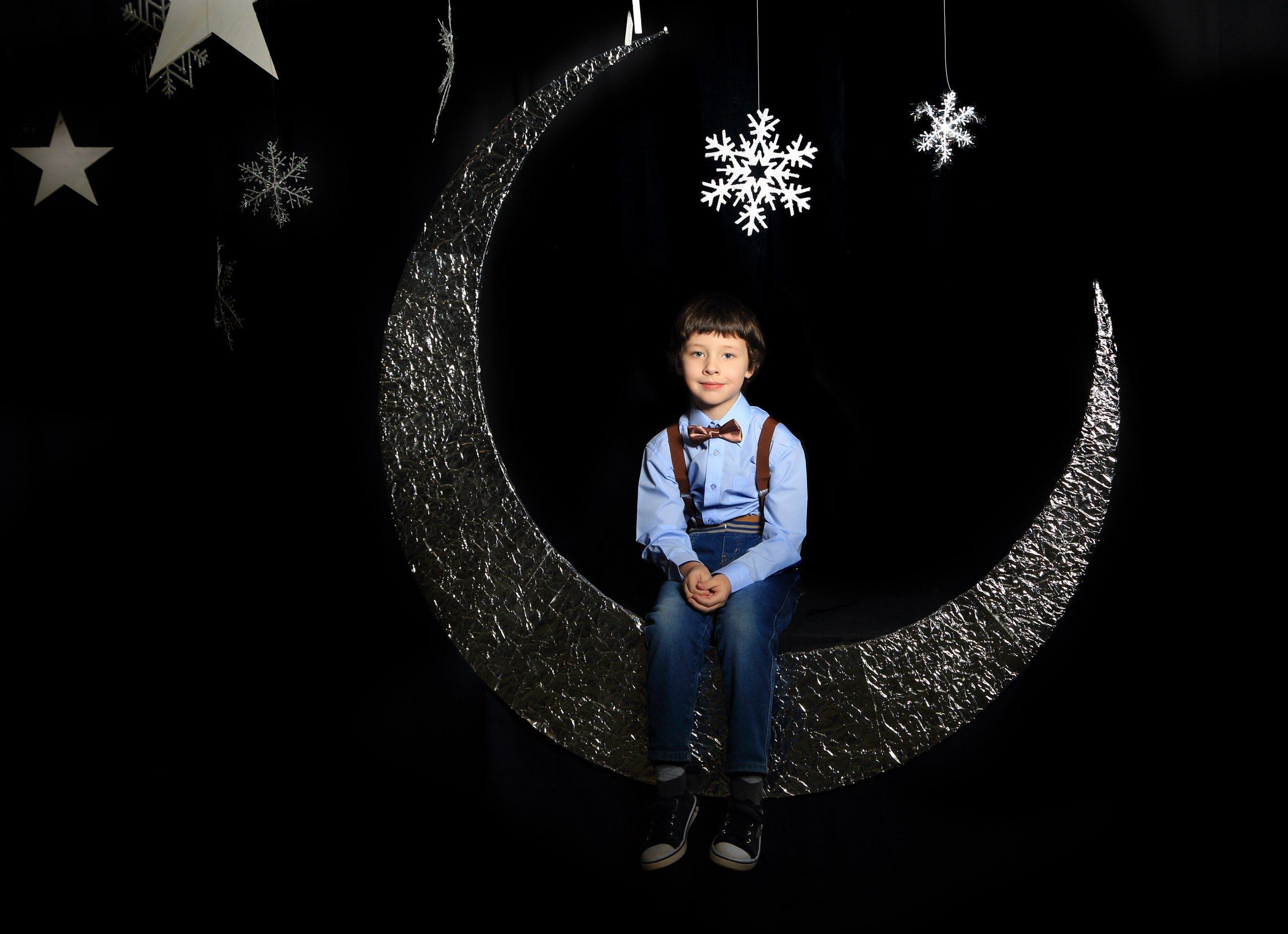 Boy Sitting on Moon Decor