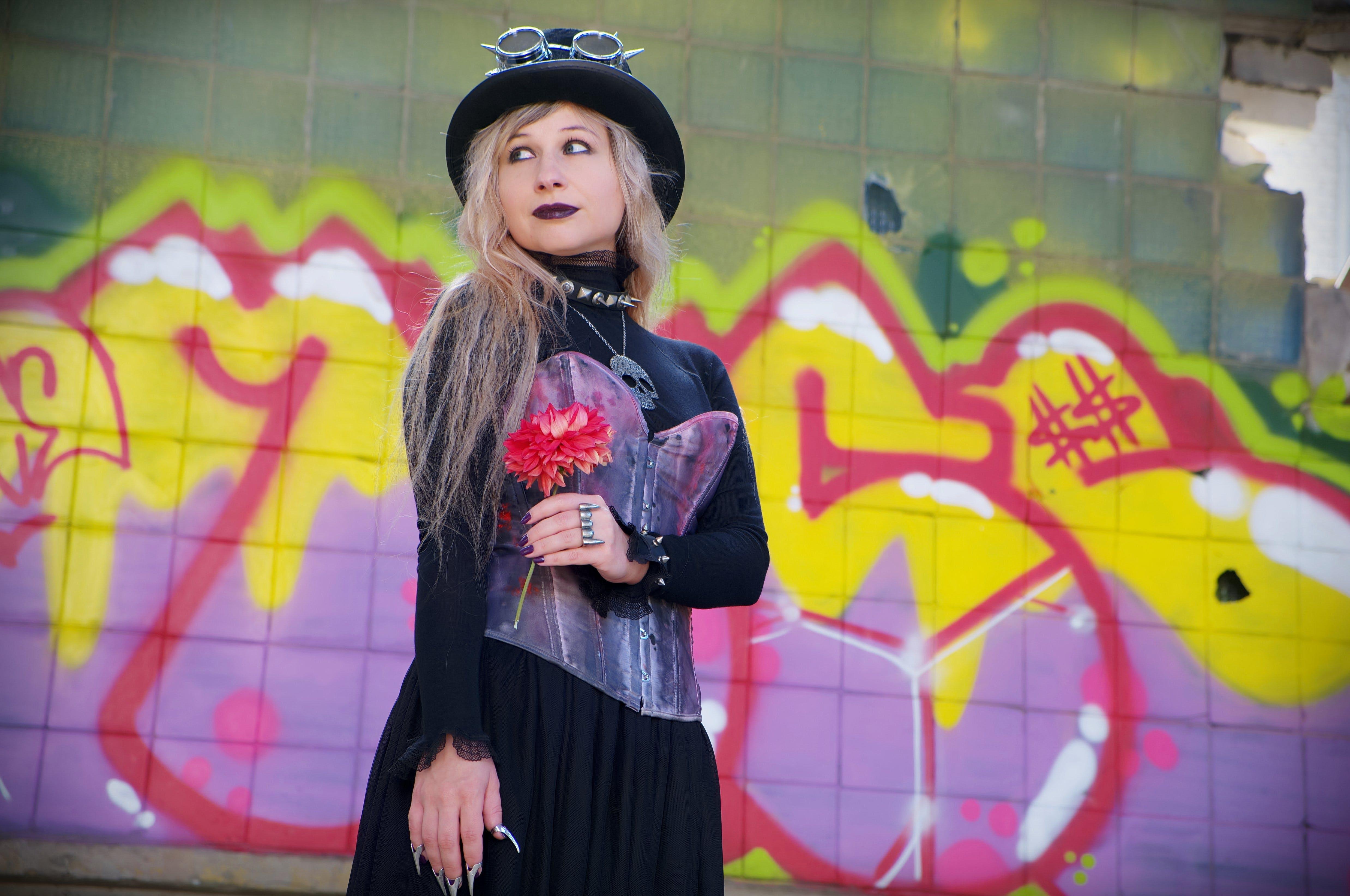Photo of Woman Standing Near a Wall With Graffiti