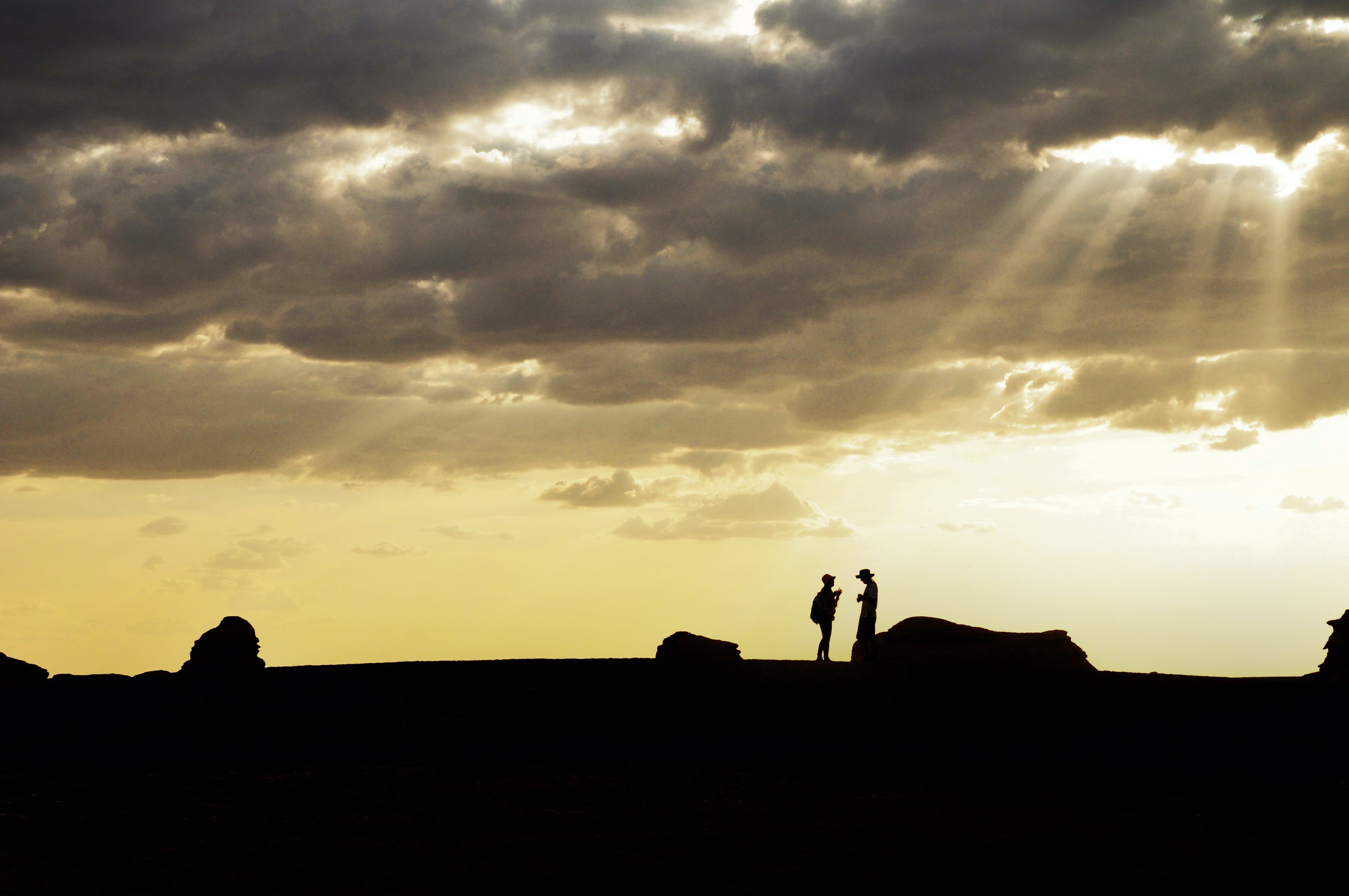 Silhouette of Two People Standing on High Ground