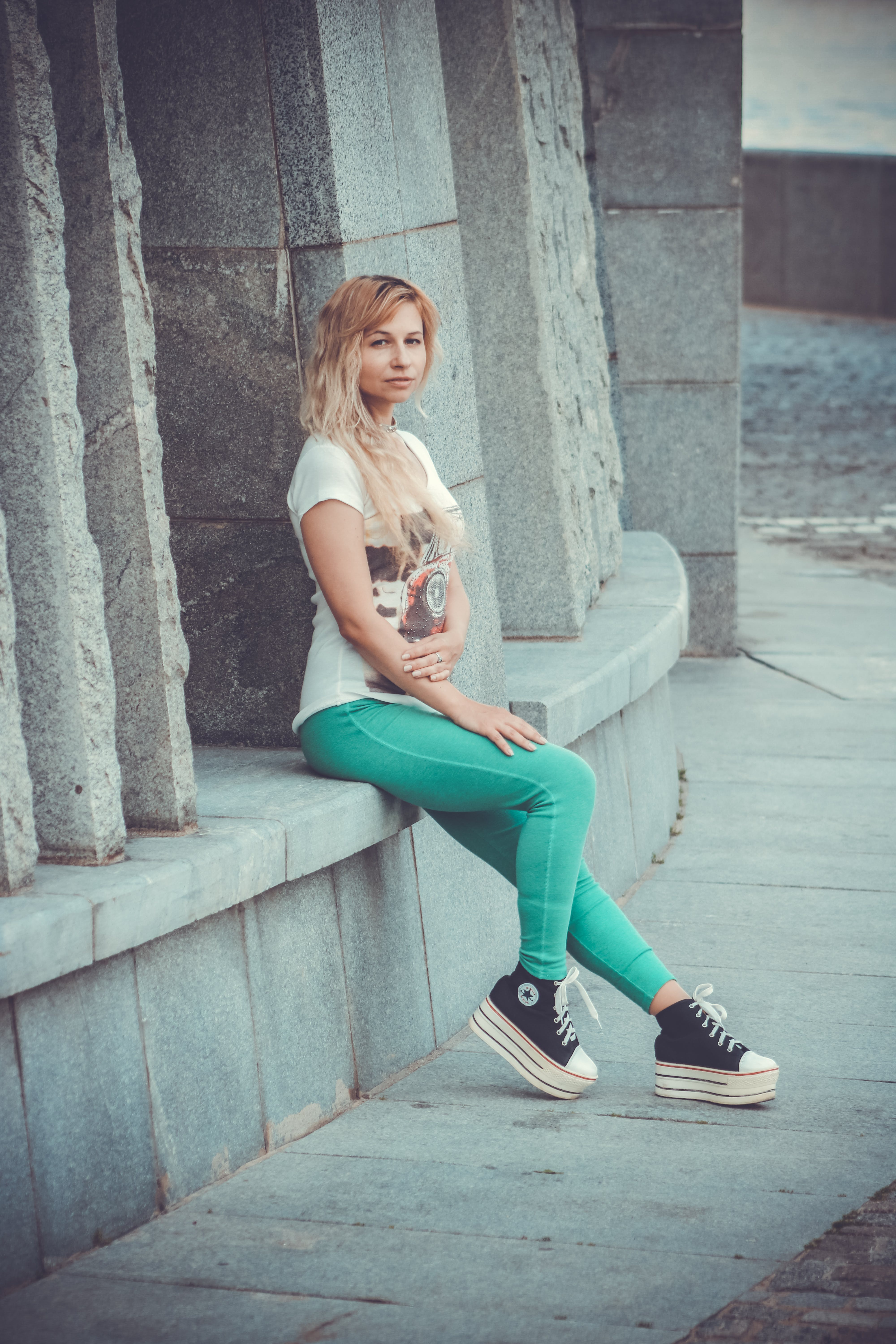 Woman Wearing White T-shirt and Green Pants Sitting on Bench