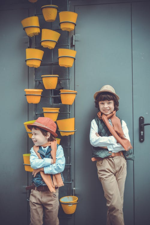 Two Boys Leaning On Wall Beside Pot Plants