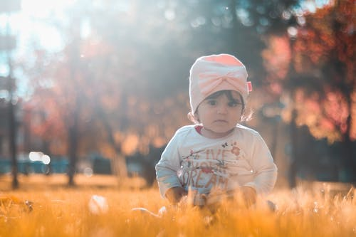 Photo of Toddler Sitting on Grass