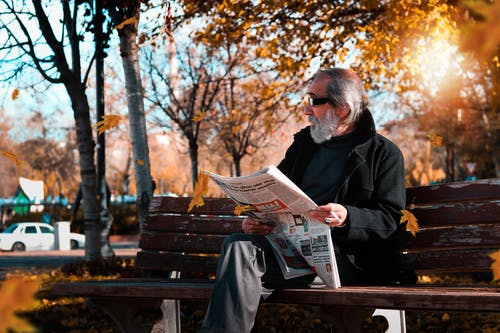 Photo of Man Holding Newspaper While Sitting on Park Bench.