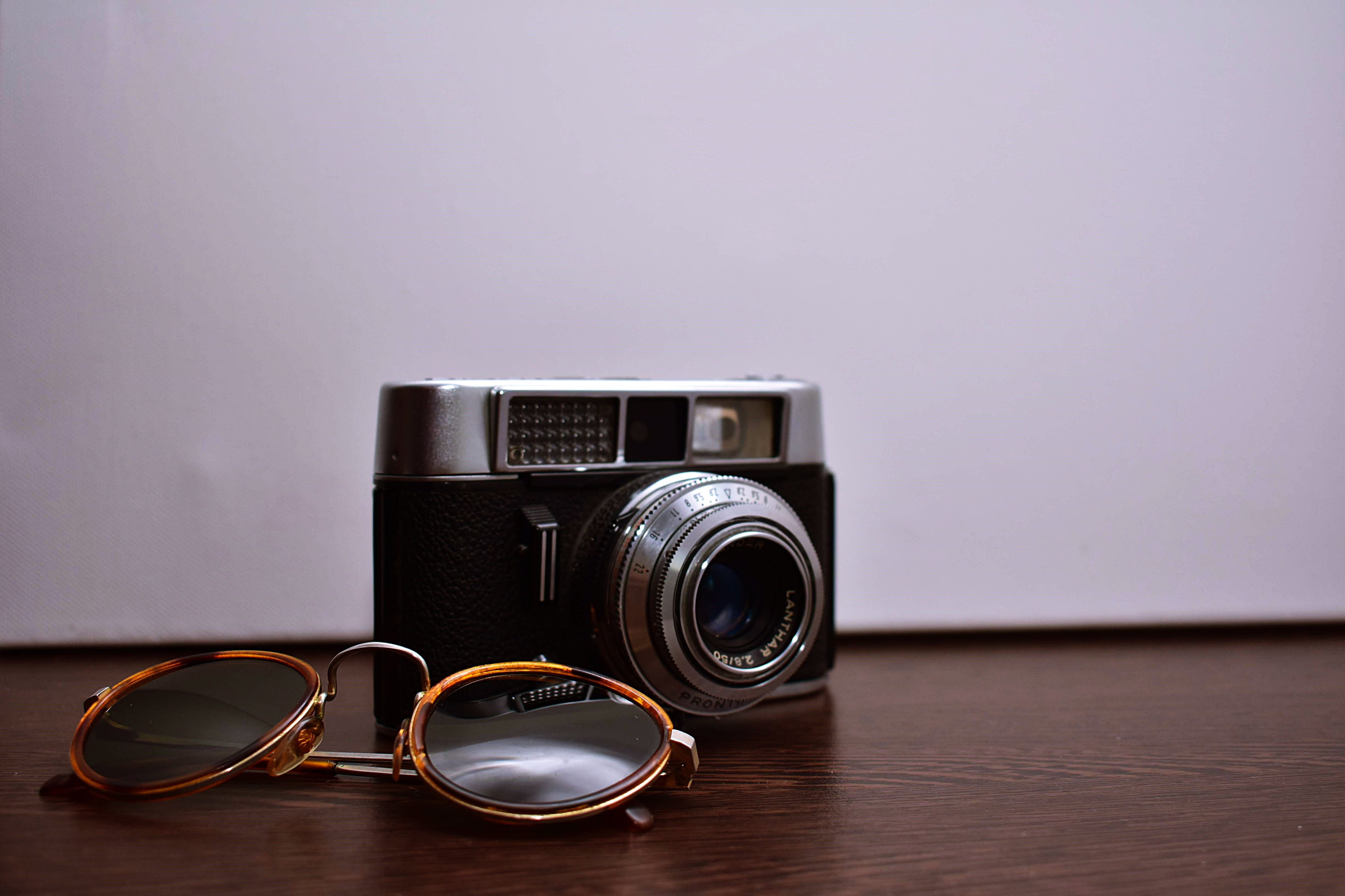 Silver and Black Dslr Camera With Brown Sunglasses on Brown Wooden Surface