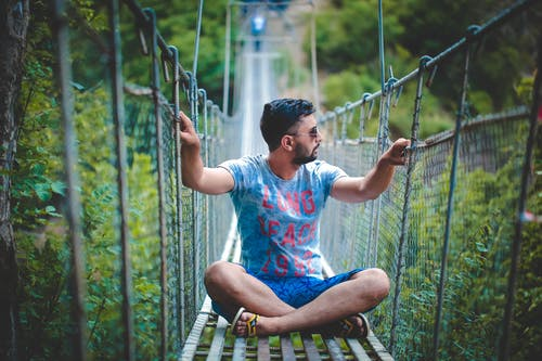Photo of Man Sitting on Hanging Bridge