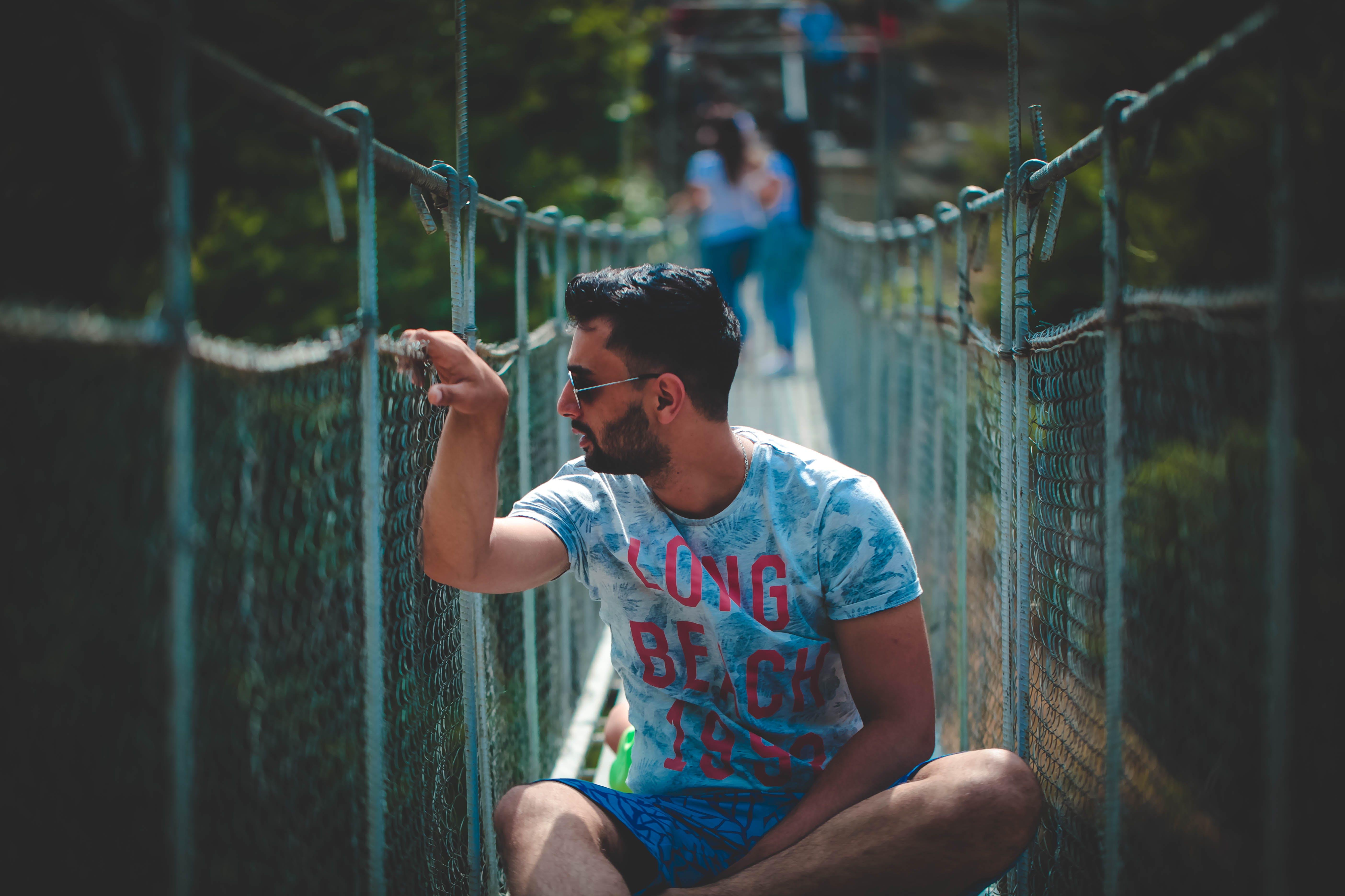Man Sitting on Hanging Bridge
