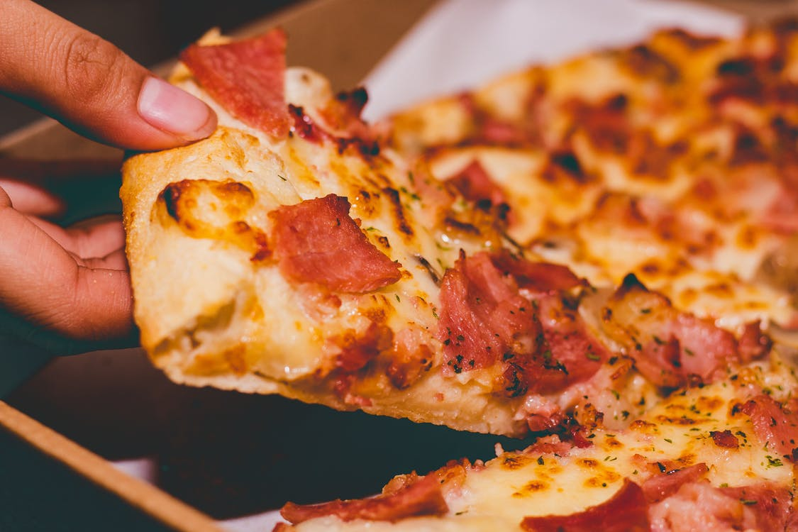 Close-Up Photo of Person Holding Pizza