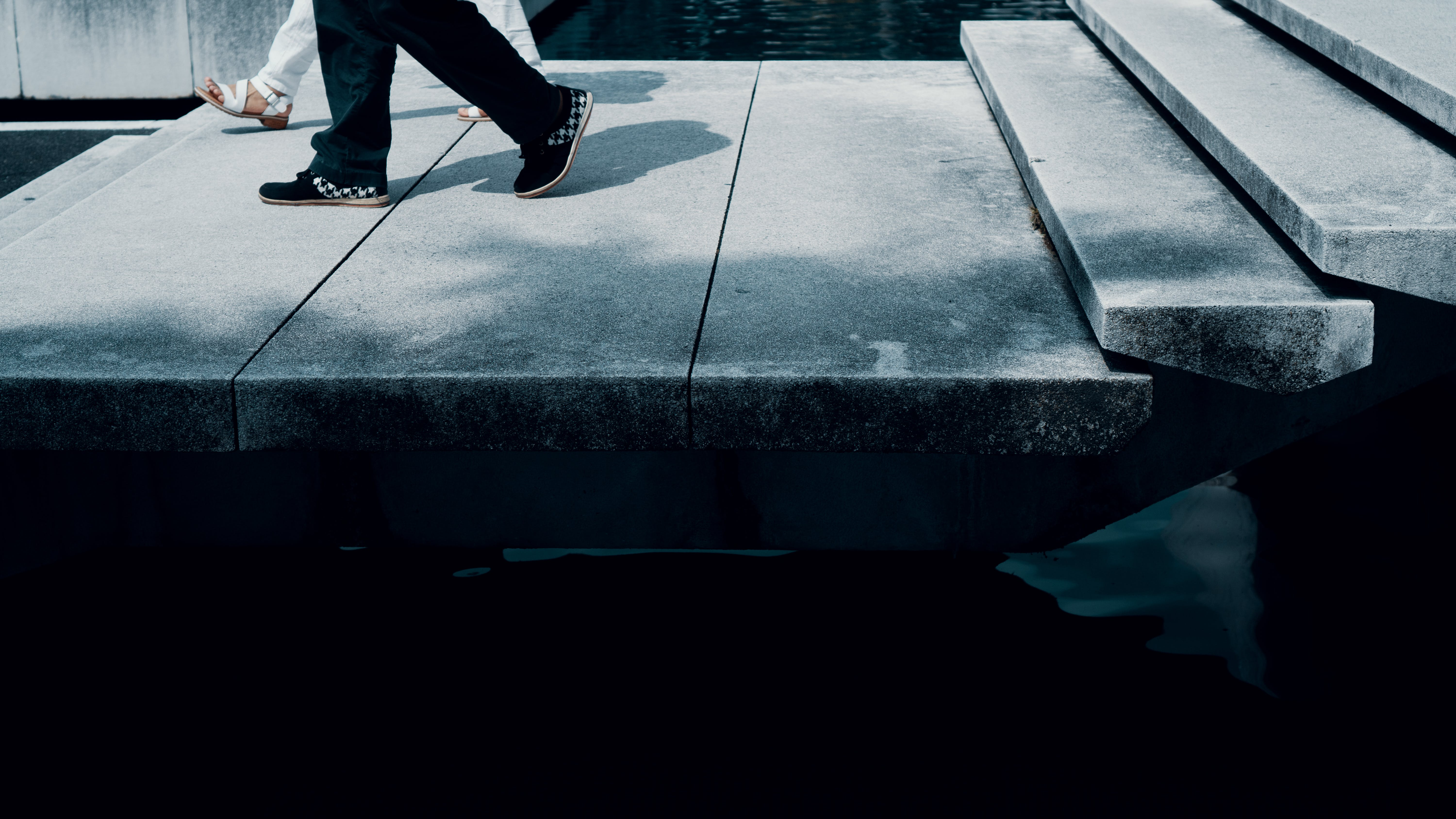 Two People Walking on Concrete Pavement