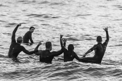 Five Surfers Having Fun on the Sea