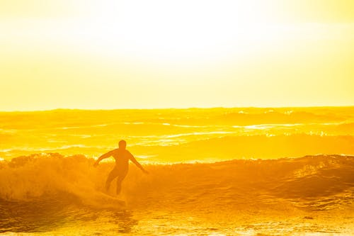 Man Surfing during Golden Hour