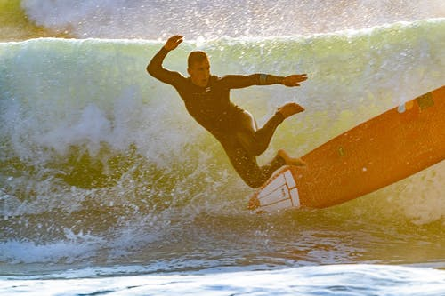 Man Jumping Off Surfboard in Sea Wave
