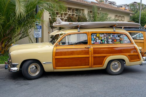 Parked Brown and Beige Station Wagon With Surfboard on the Roof