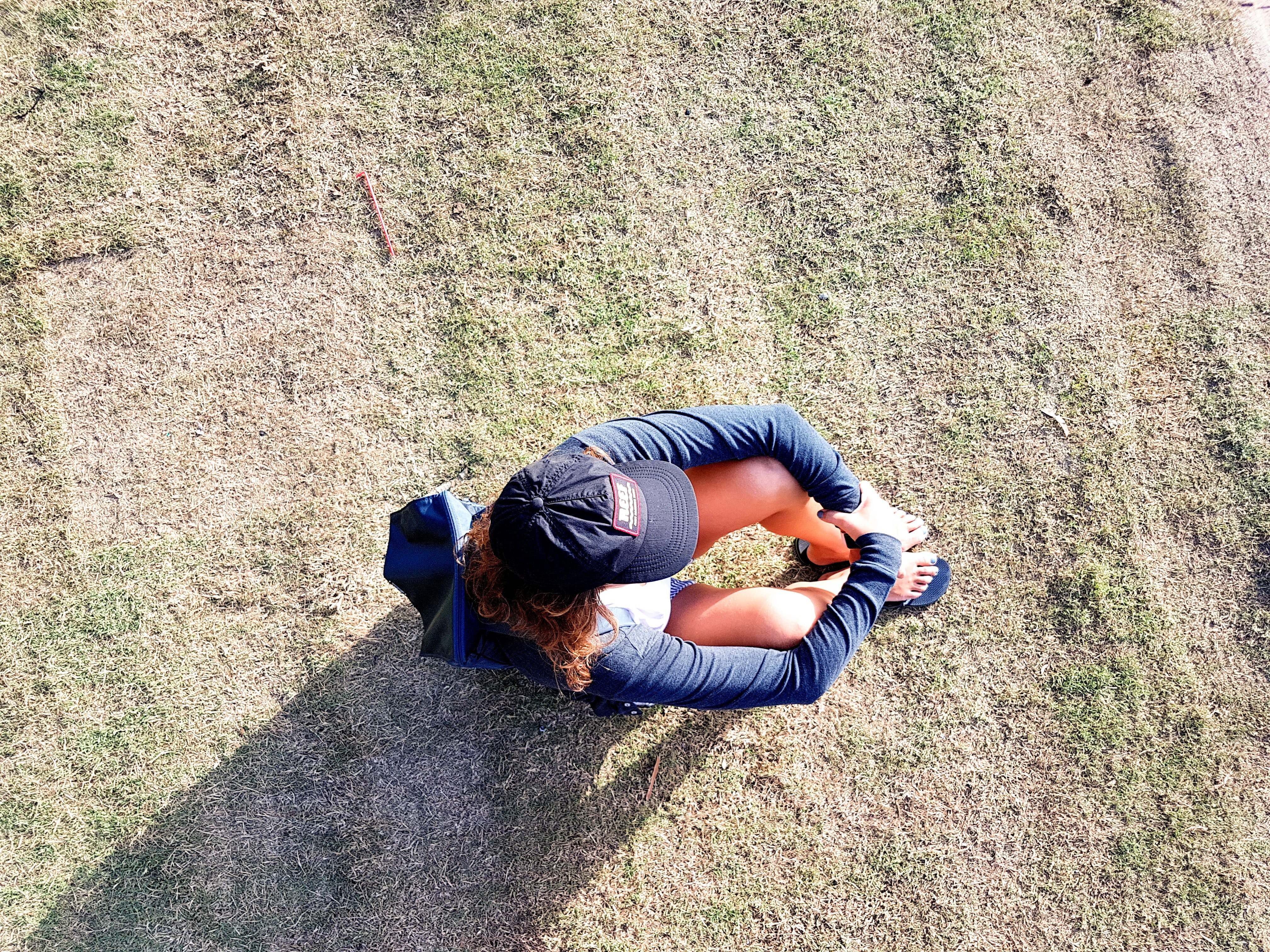Overhead Photo of Woman Sitting on Green Grass Field