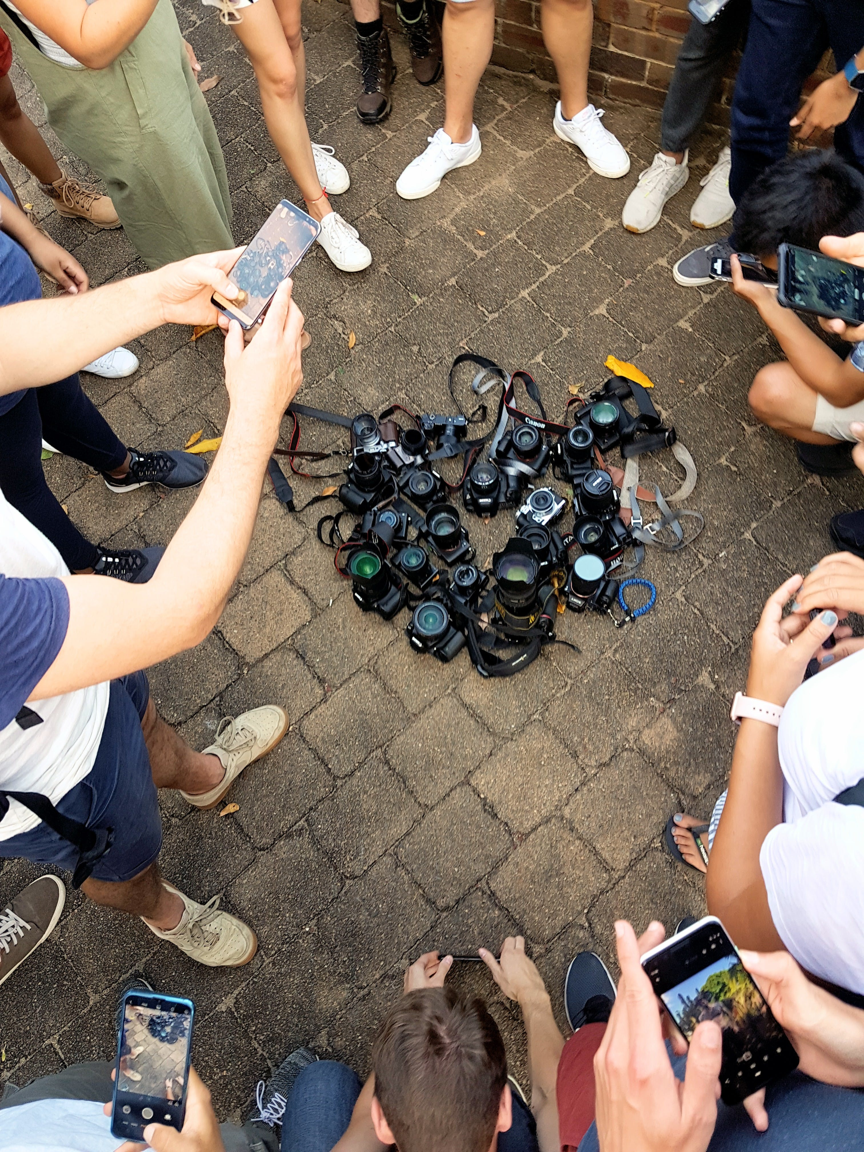 Photo of DSLR Cameras Lying on the Ground Surrounded by People