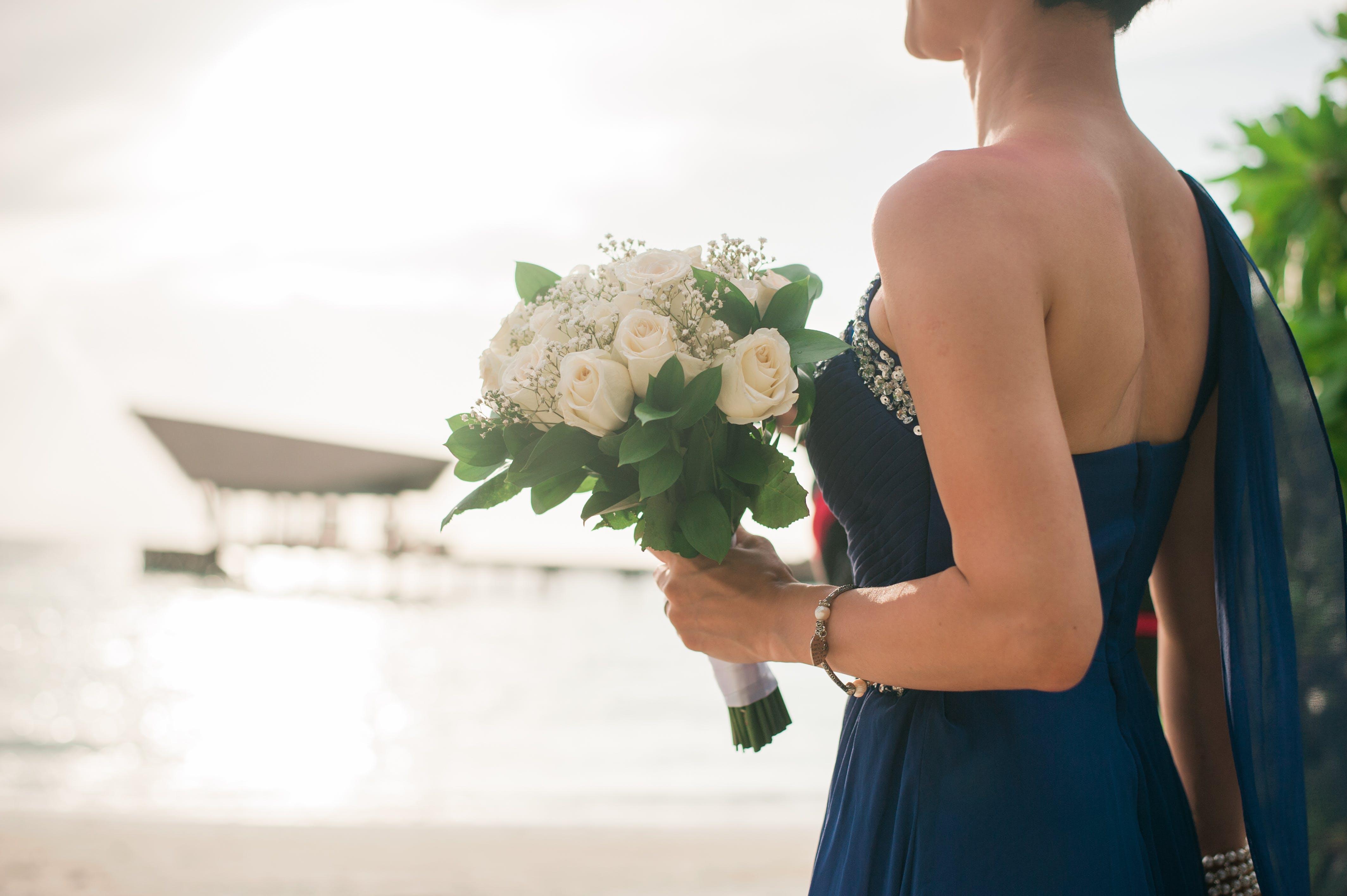 Woman Wearing Blue Dress Holding White Petaled Flower Bouquet