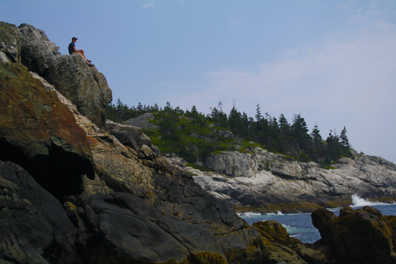 Man Sitting on Mountain Cliff