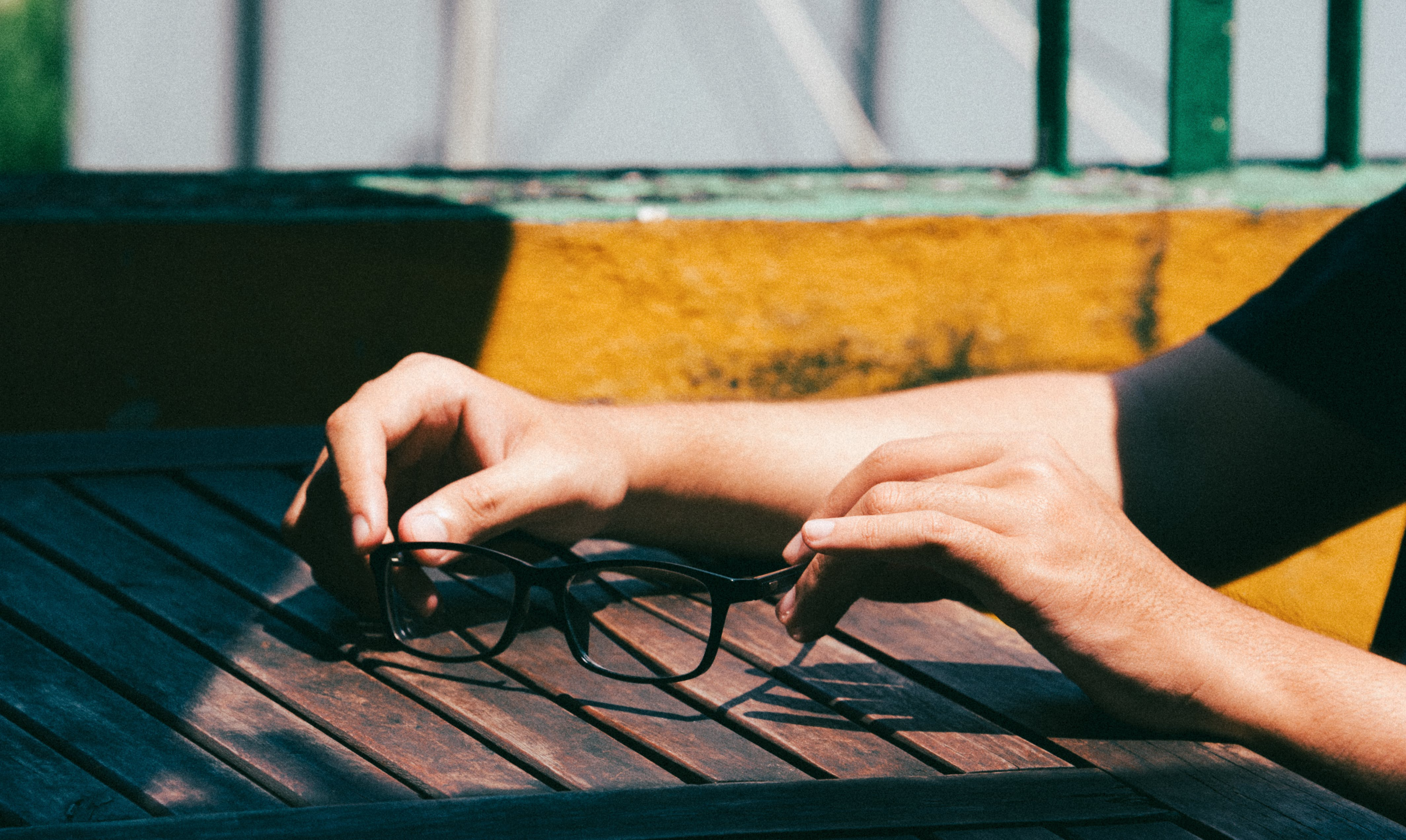 Photo of a Person's Hands Holding a Black Framed Eyeglasses