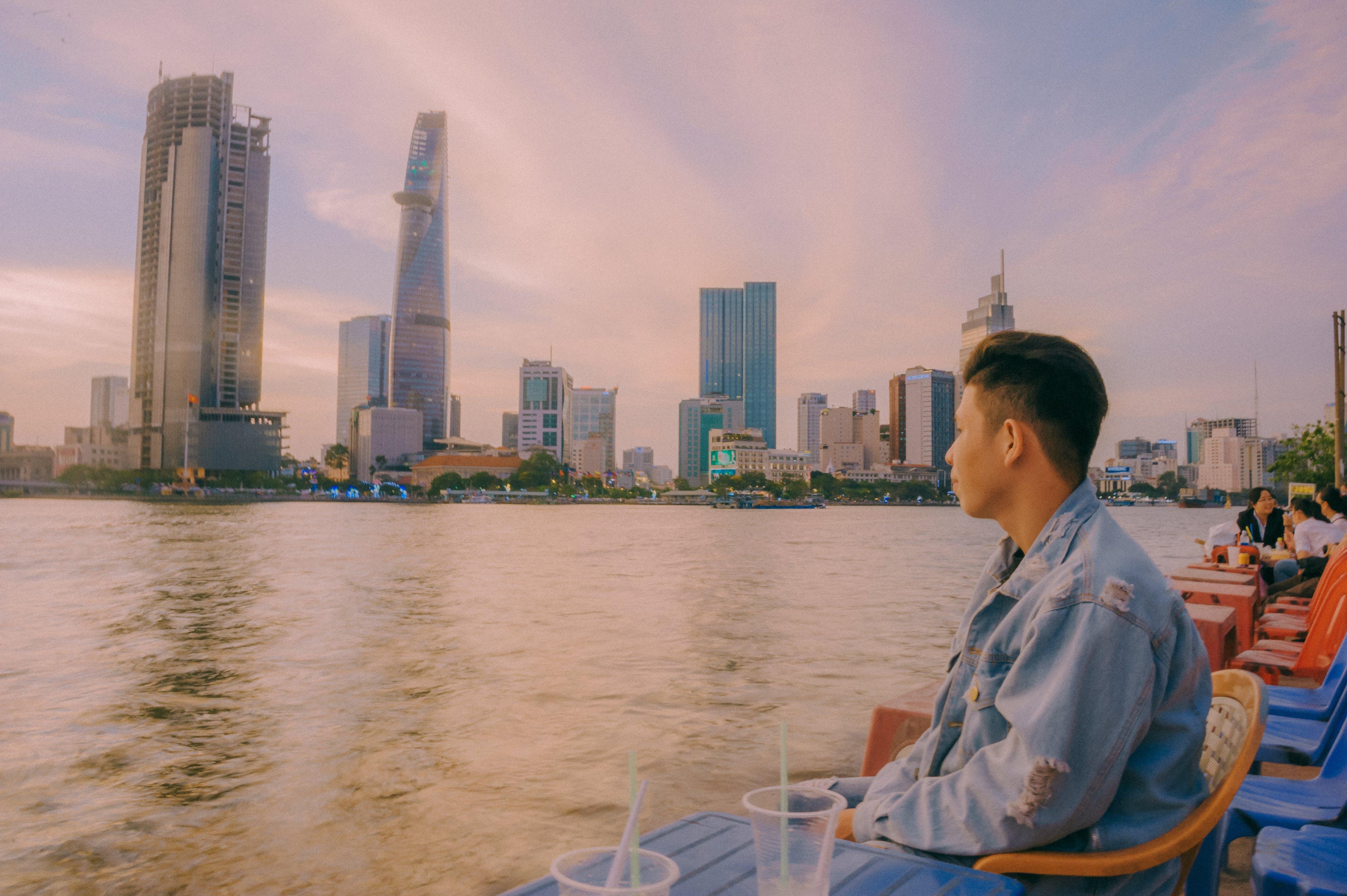 Man in Denim Jacket Sitting Near Body of Water