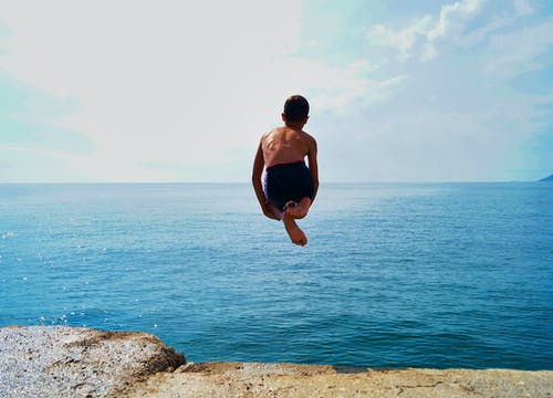 Time Lapse Photography of Boy in Black Shorts Jumping on Body of Water