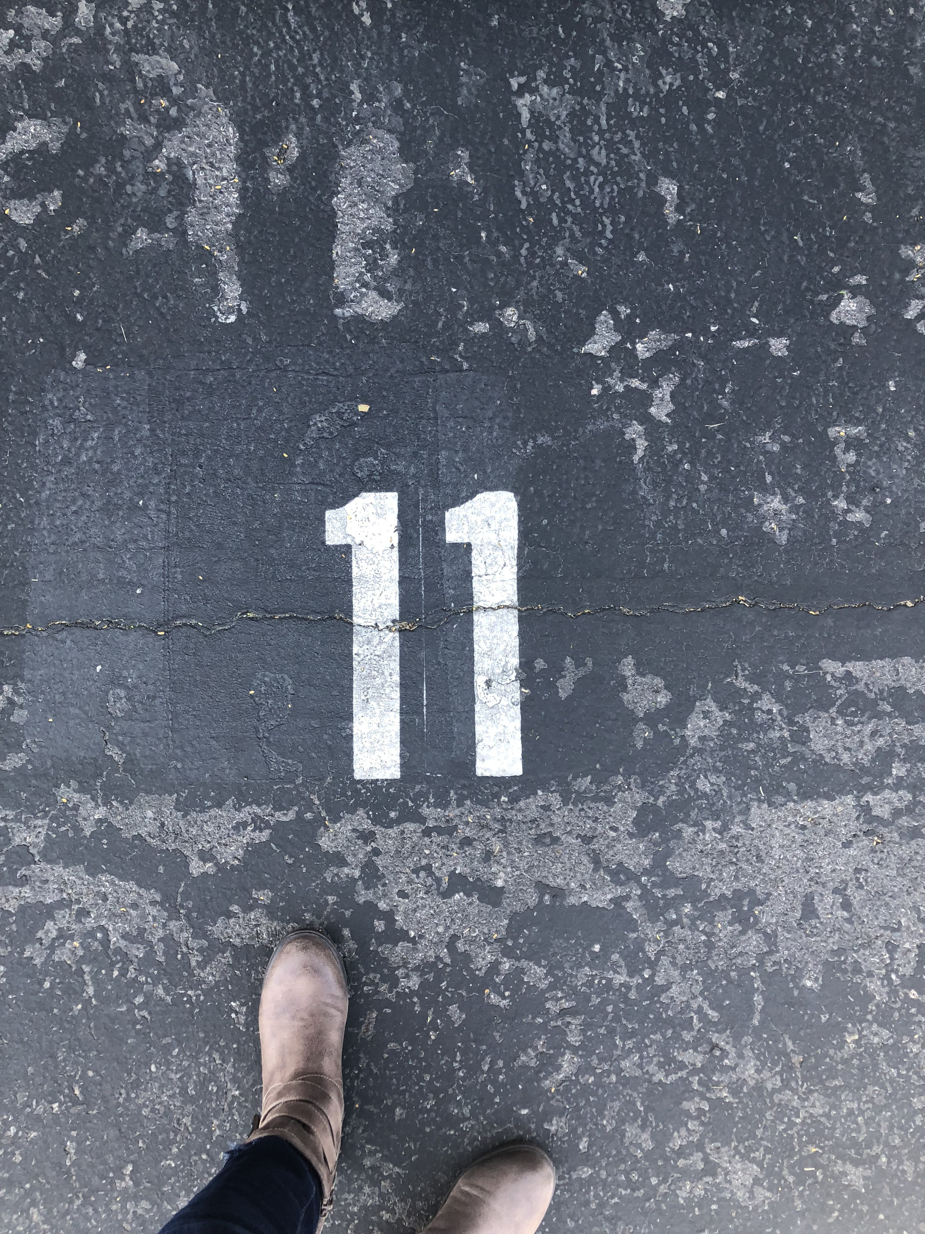 Person Standing On Concrete Floor With Number 11 Paint