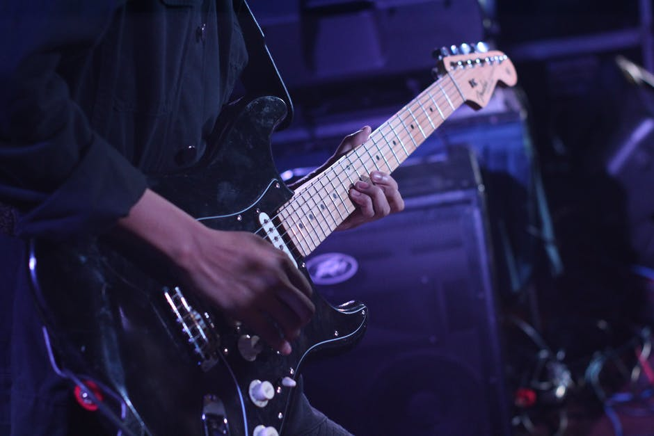 Person using black fender stratocaster