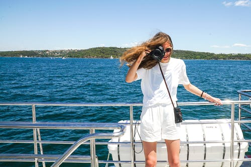 Woman Capturing Photo While Holding Hand Rails on Boat