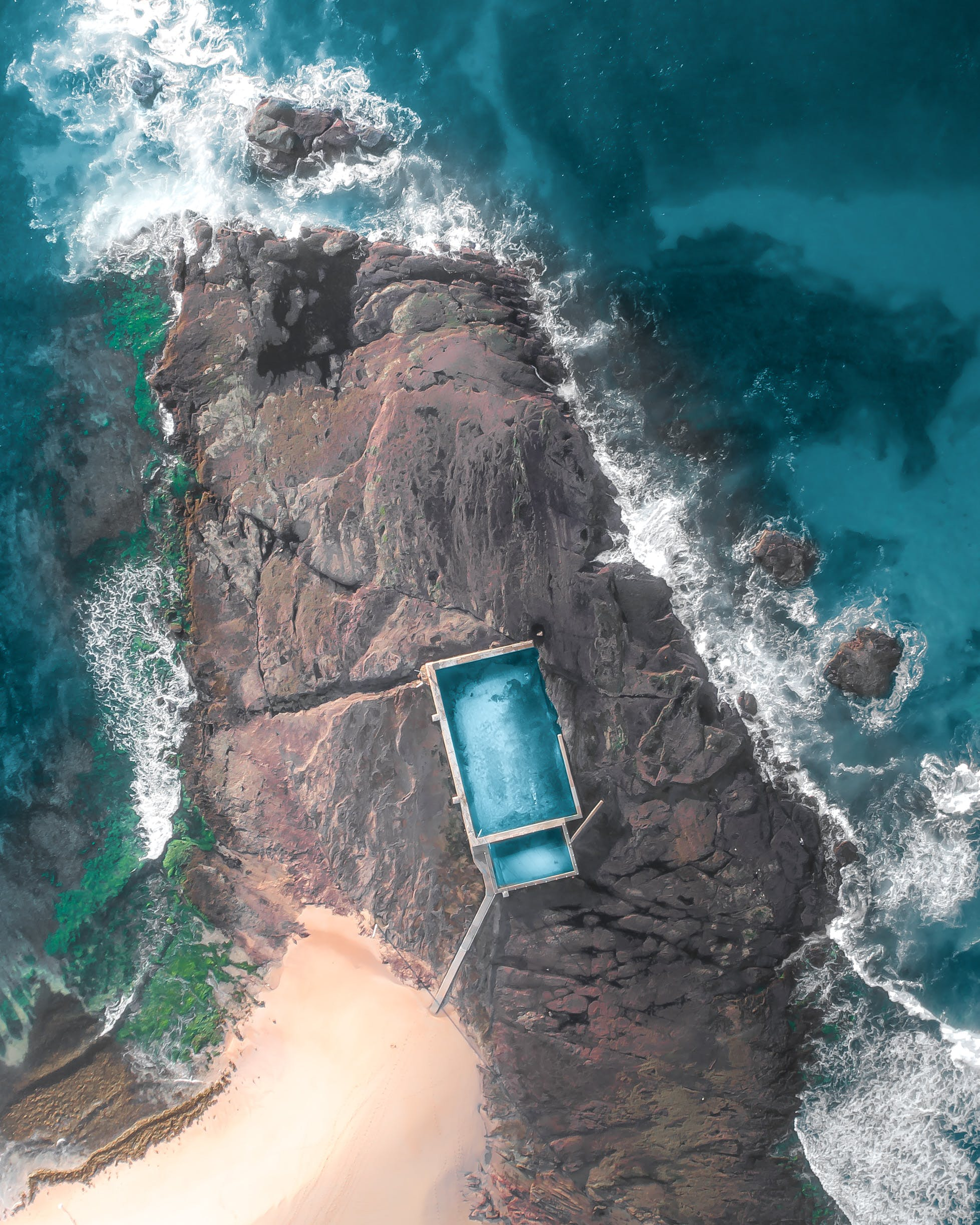 Aerial Photography of Teal and White House on Rock Formation Near Body of Water