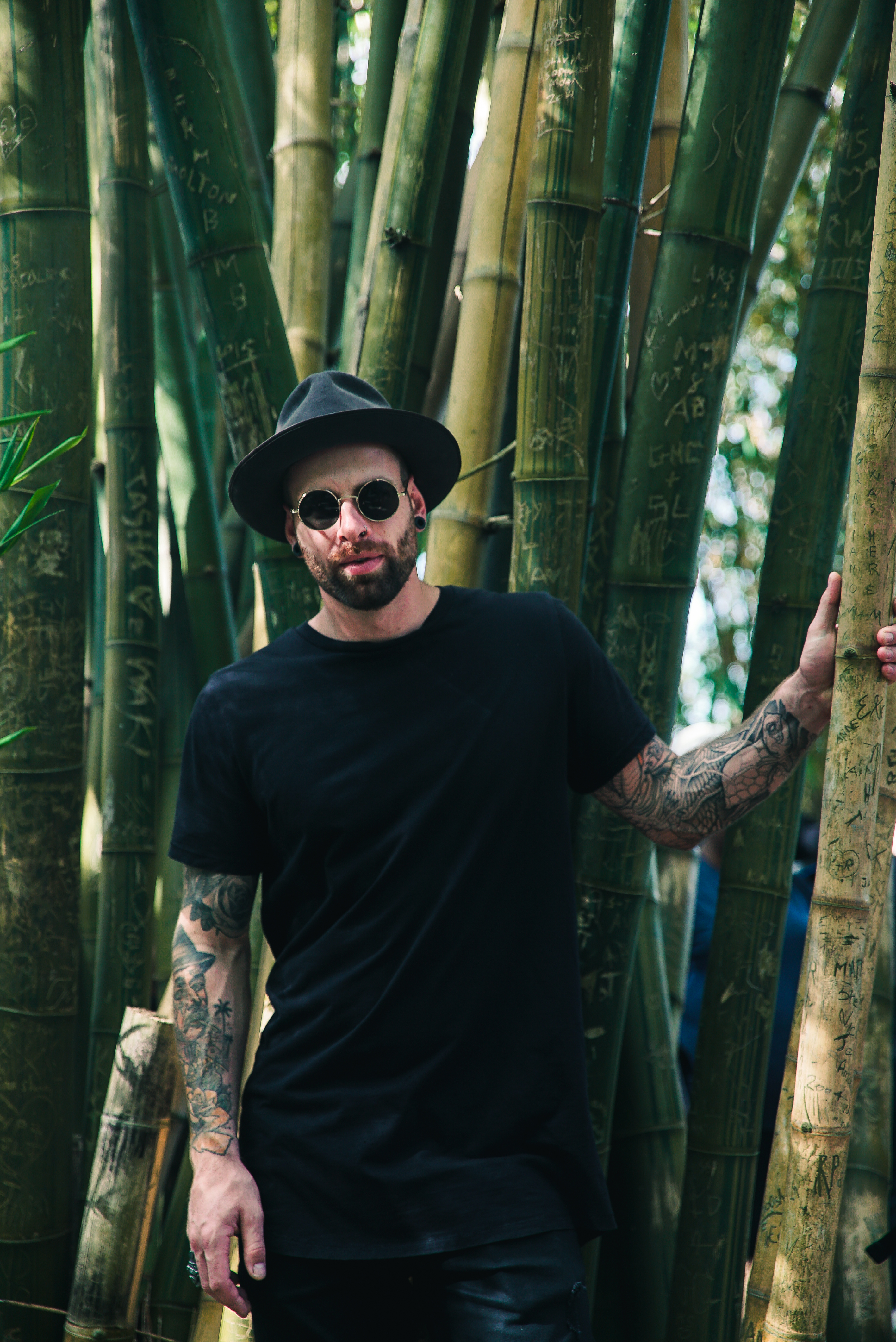 man holding bamboo plant wearing sunglasses and fedora hat