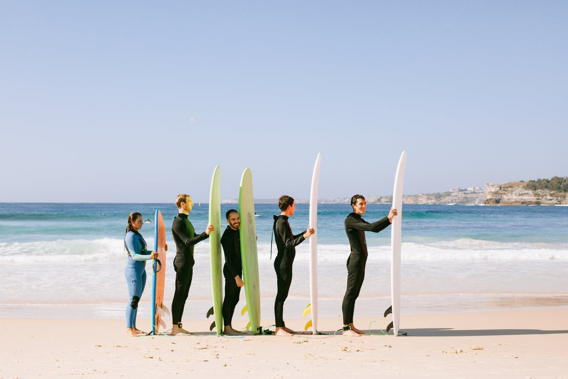 Group Of Five People Standing in Line While Holding Surfboards Near Seashore