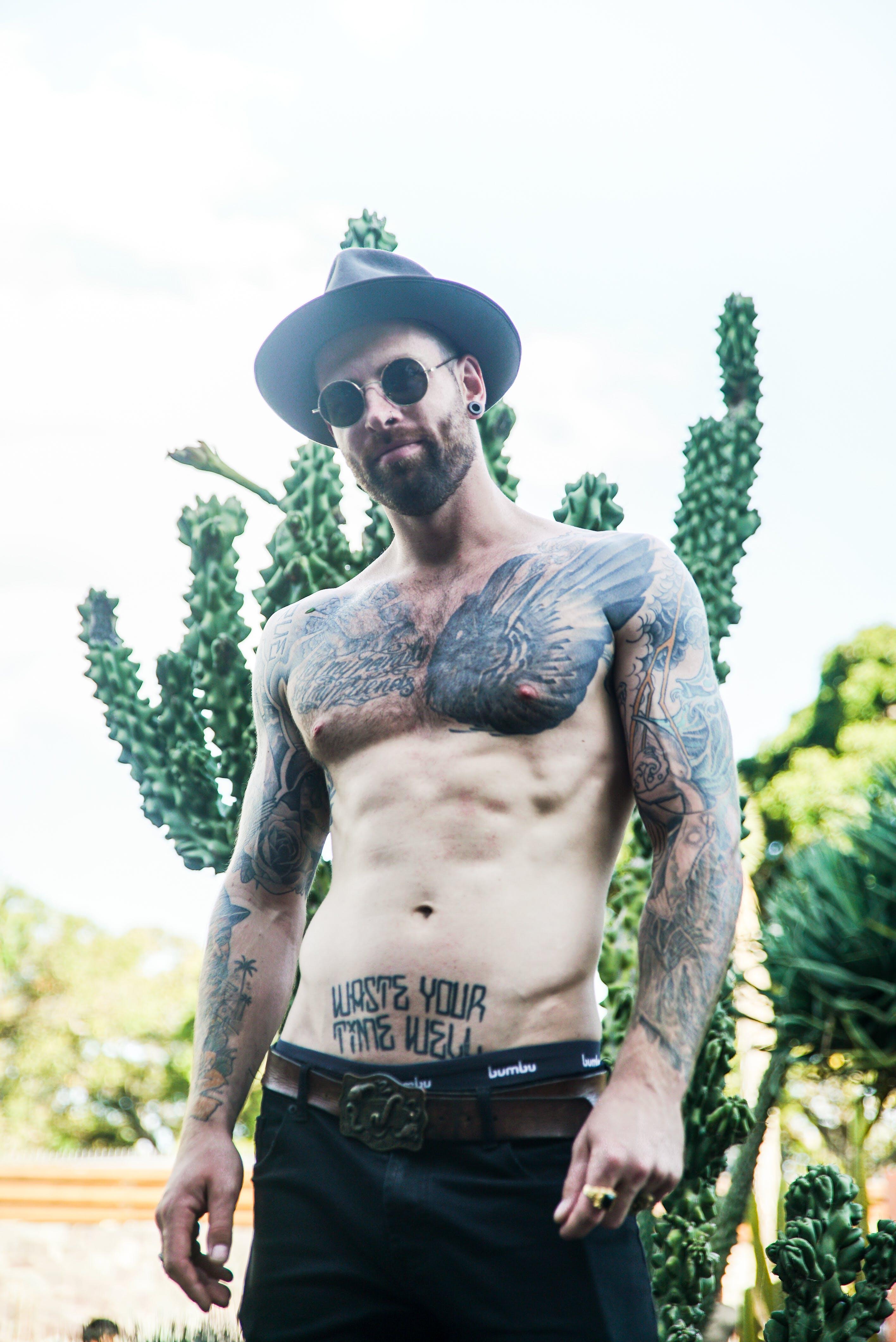 Man Wearing Sunglasses Standing Near Plant