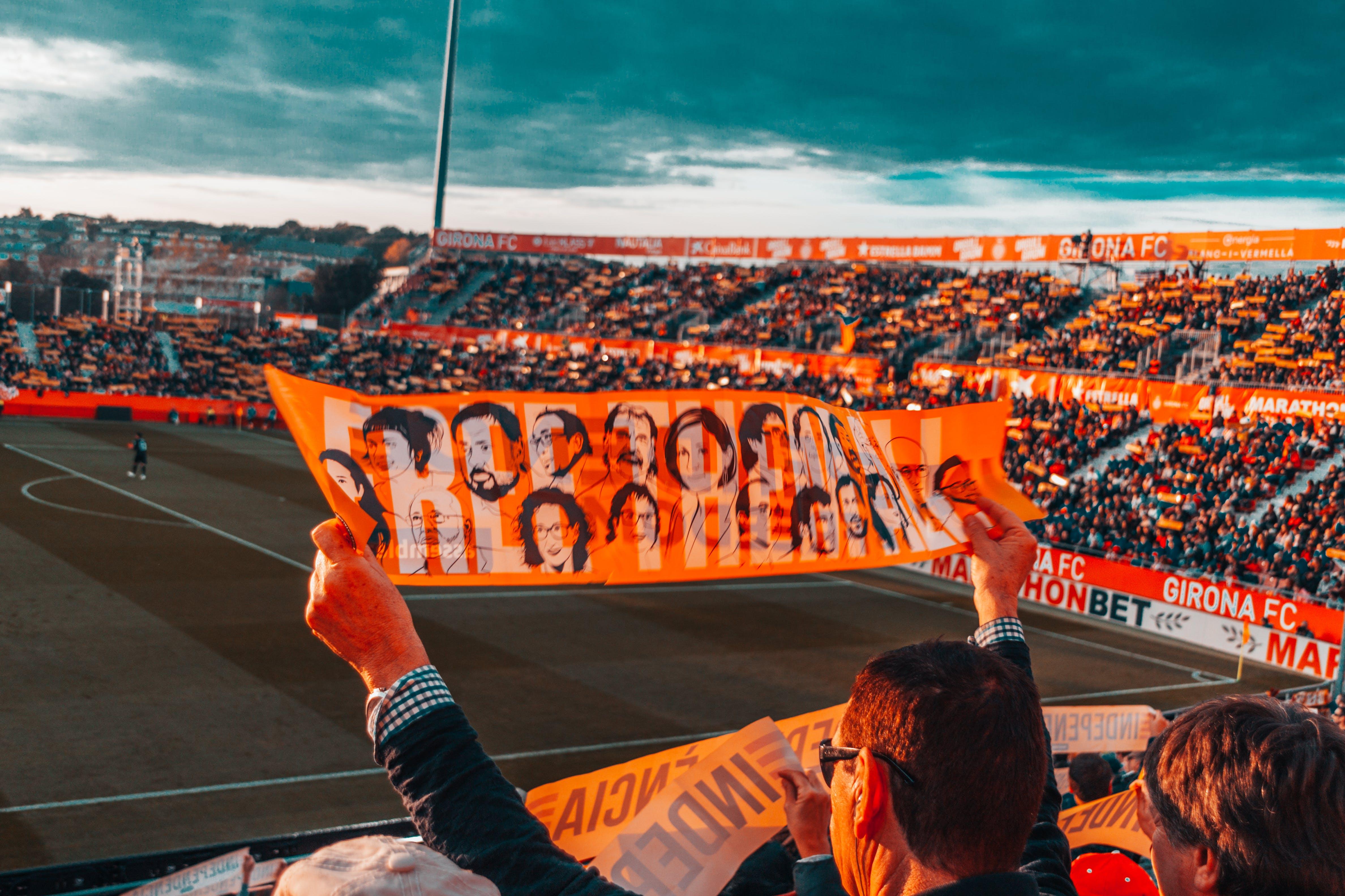 Person Holding Orange Banner on Stadium