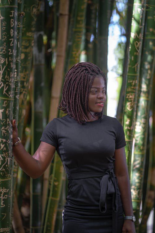 Smiling Woman Standing Near Bamboo Trees