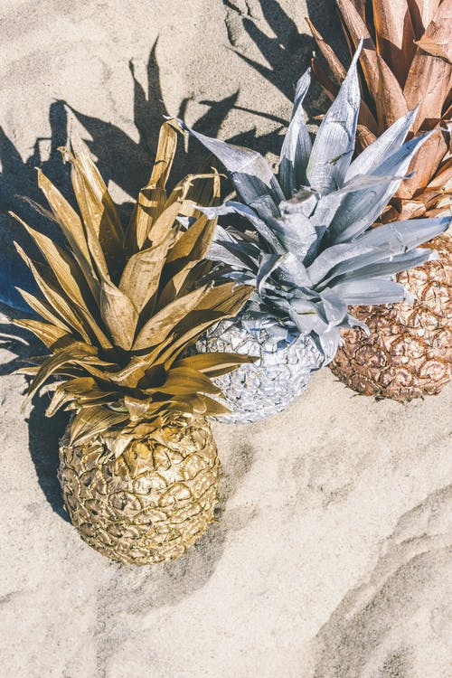 Close-up Photo of Three Painted Pineapple Fruits on Beach Sand
