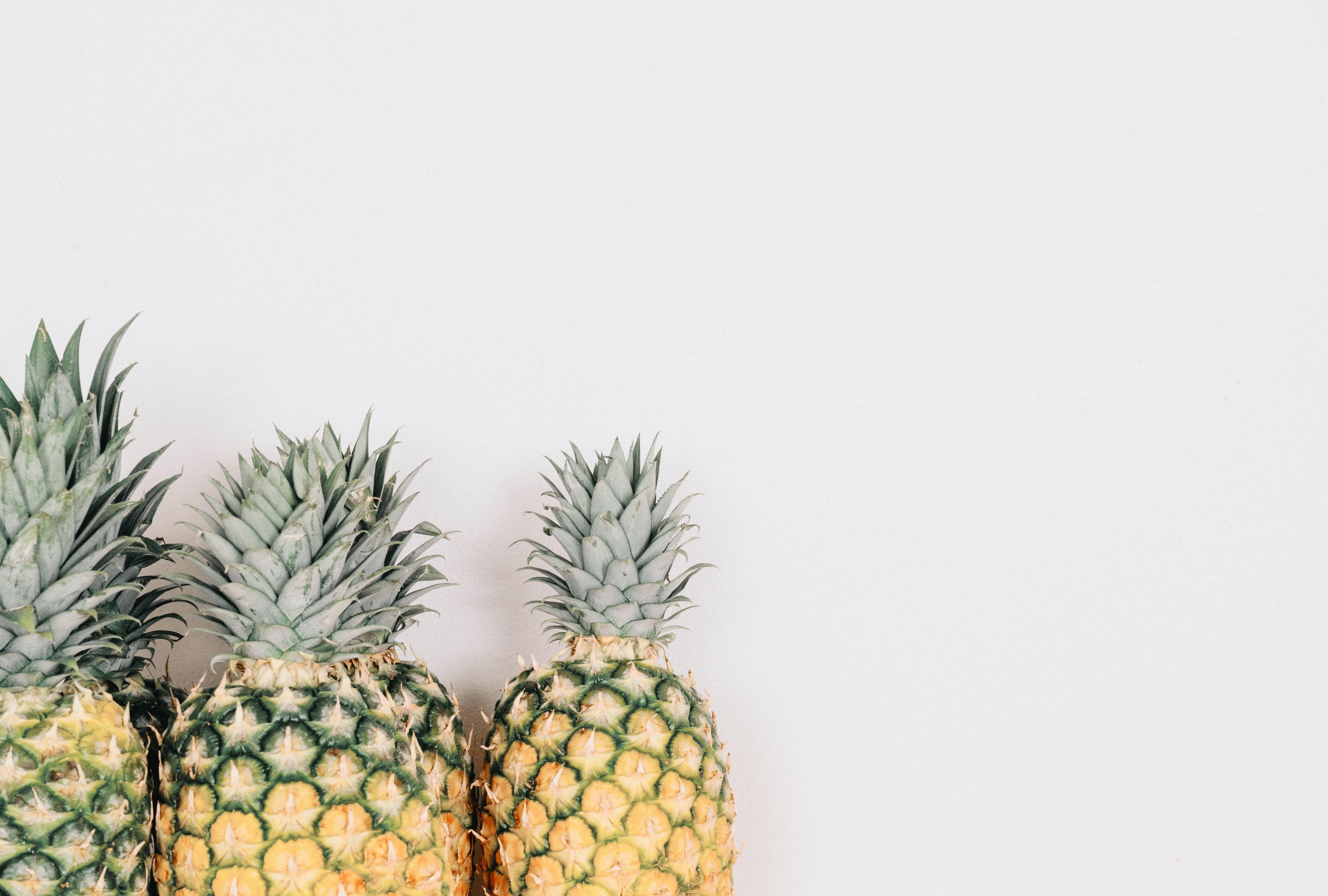 Three Pineapples Near White Wall