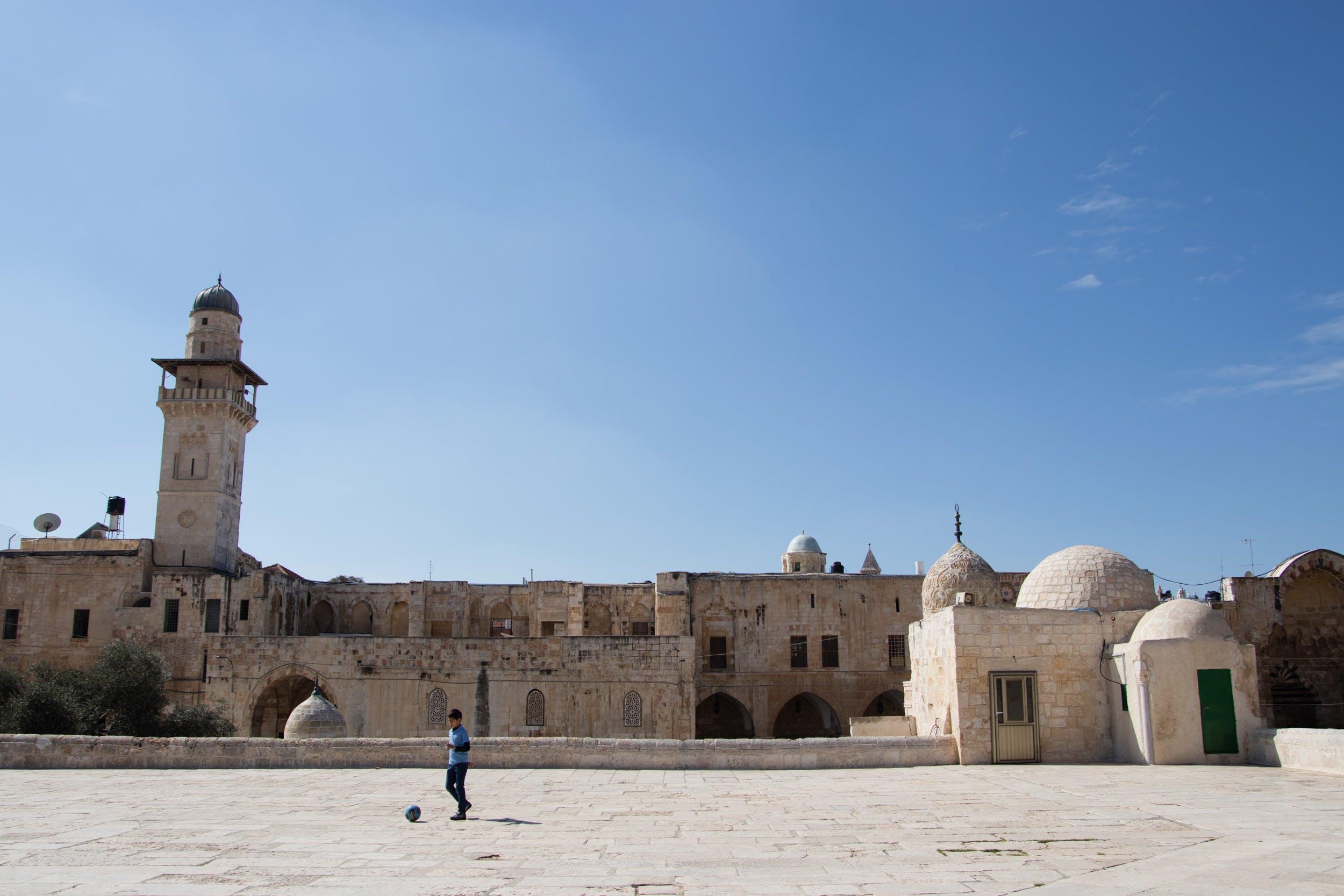 Man Playing Ball Near White Concrete Mosque