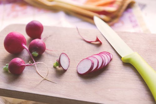 Green and Silver Kitchen Knife Beside Pink Onions