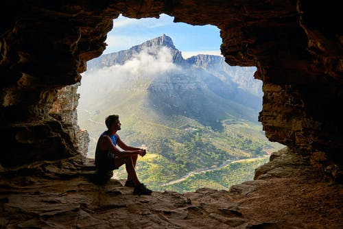 Photo of Man Sitting on a Cave