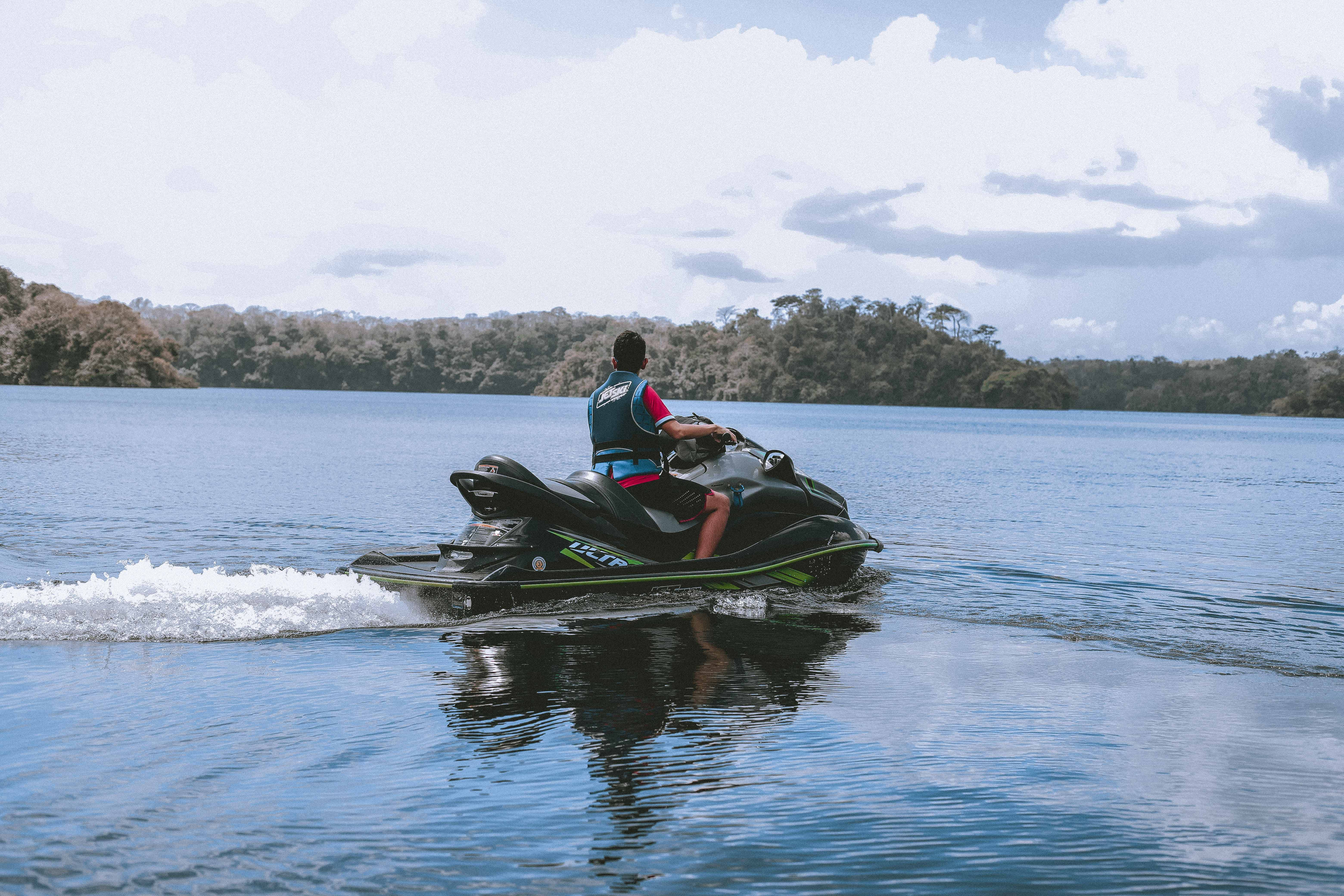 Man Riding on Green Personal Watercraft on Body of Water