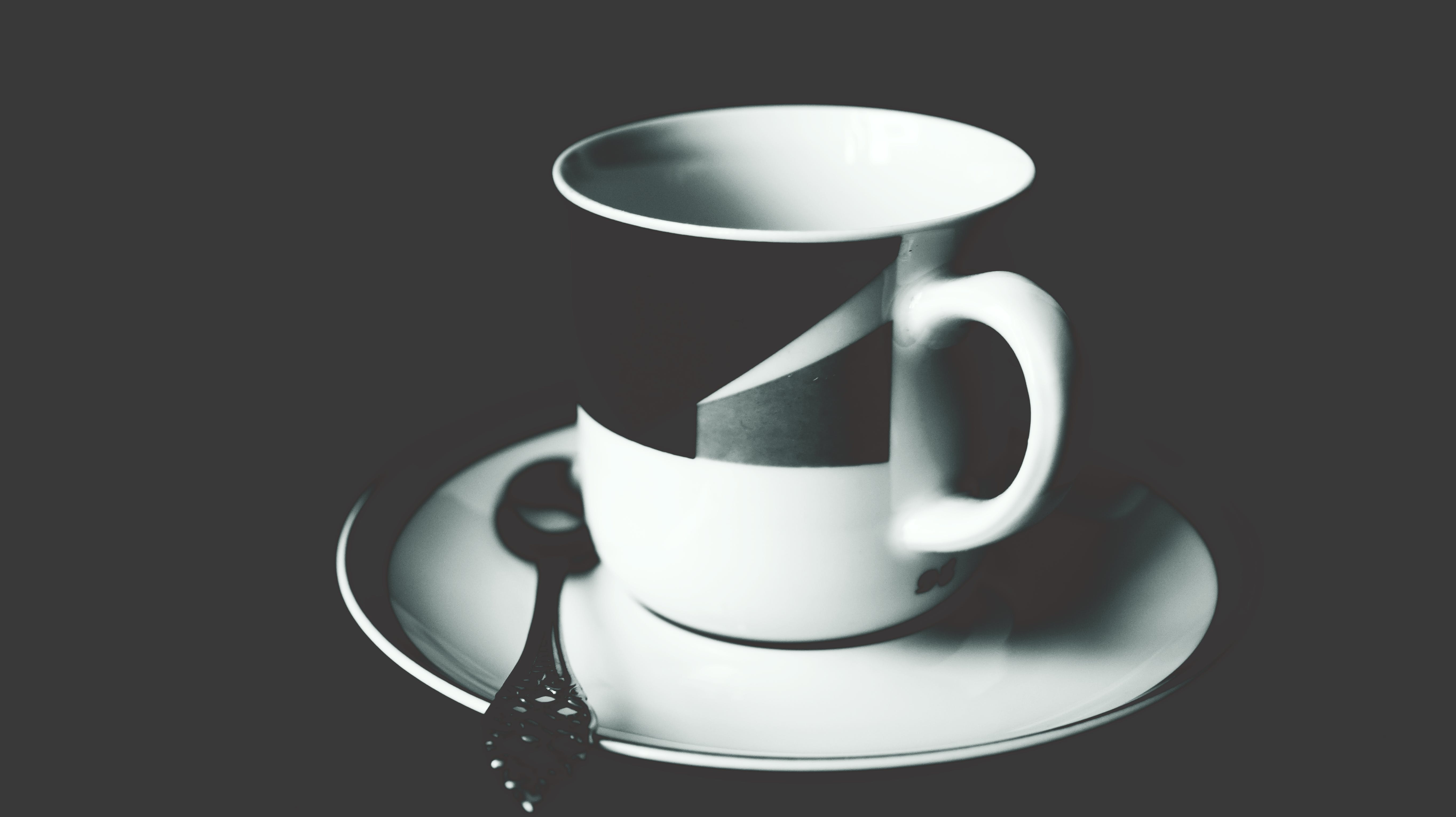 White and Black Ceramic Tea Mug on White Ceramic Round Plate and Stainless Steel Spoon on Top