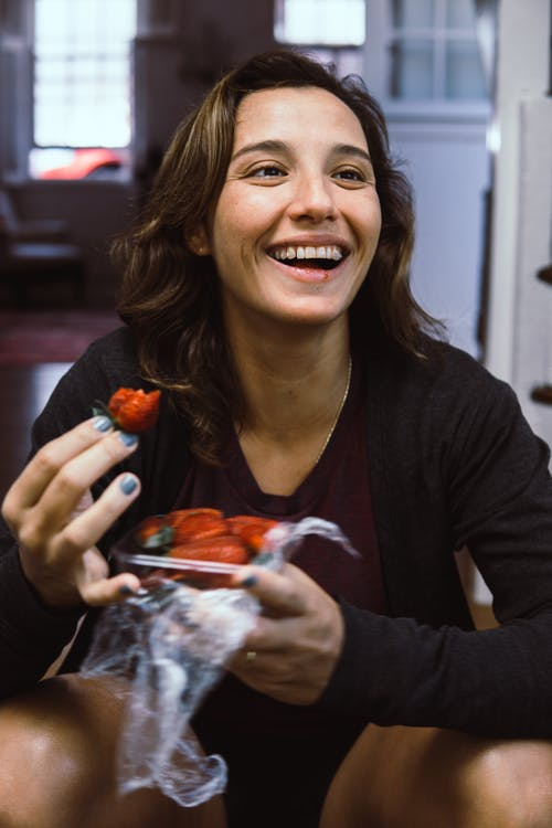 Woman Eating Strawberry Indoors