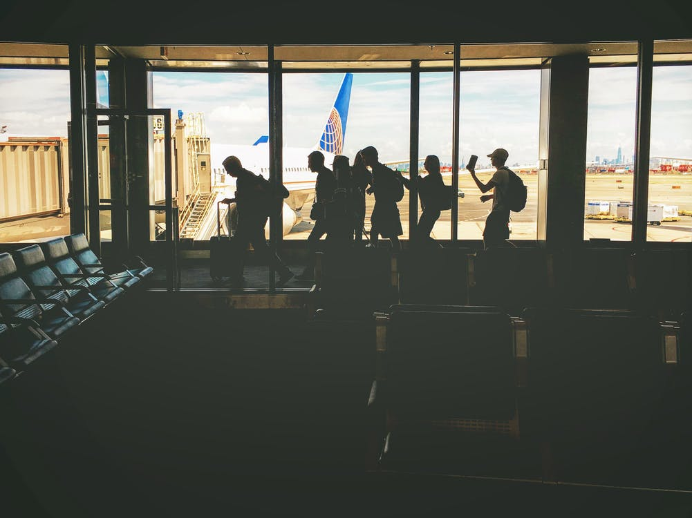 Group of People Walking Near Clear Glass Window With a View of White Airplane Parked during Daytime